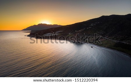 Scenic view of sunset by mountains and sea