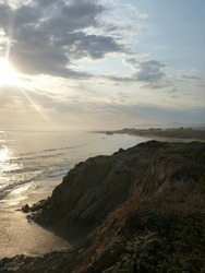Scenic view of the coastal bluffs and Pacific Ocean waves at Big Sur near sunset