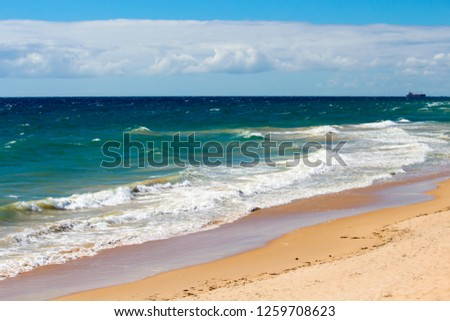 Scenic view of the Indian Ocean waves breaking on the sandy shore at Ocean Beach Bunbury Western Australia on a cloudy morning in early autumn creates a splendid sea scape. #1259708623