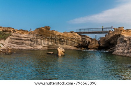 Scenic view of the Lion's Head Rock inside the pond. In the background, the beautiful sandstone layers can be admired and visitors are taking photos on the footbridge at Yehliu Geopark, Taiwan. #796565890
