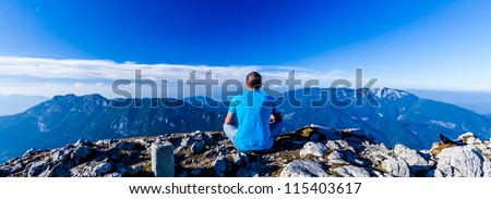 Scenic view of the man who meditates sitting on the cliff`s edge on the wide mountains landscape background. Velika Raduha, Slovenia.
