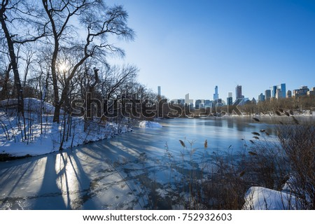 Scenic view of the Midtown skyline reflecting in the ice of the frozen Central Park lake the morning after a winter snow storm in New York City #752932603