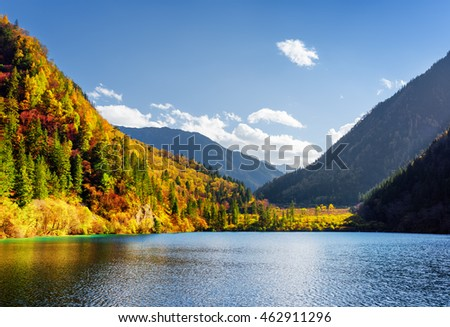 Stock Photo Scenic view of the Panda Lake among colorful fall woods and mountains at the Rize Valley in Jiuzhaigou nature reserve (Jiuzhai Valley National Park), China. Beautiful sunny autumn landscape.