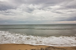 Scenic view of the waves hitting the beach on a cloudy overcast day in the village of Varkala in Kerala, India.