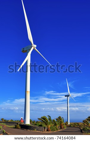 Scenic view of two wind turbines with blue sky and cloudscape background on island on Lanzarote, Canary Islands, Spain.