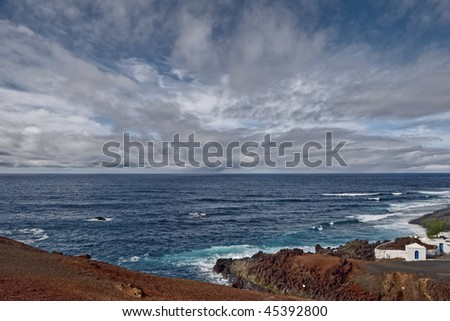 Scenic view of volcanic El Golfo coastline under cloudscape, Lanzarote, Canary Islands, Spain.