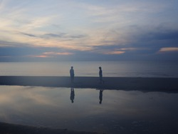 Scenic view of 2 women on beach at dawn with reflection