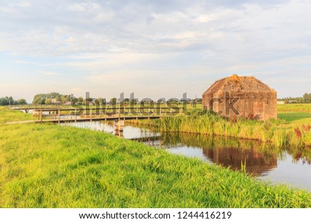 Scenic view on an abandoned blockhouse from World War II in a recreational park with meadows, green, a bridge, water near Utrecht in the Netherlands.
