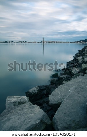 scenic view on shoreline harbor with boat pole in atlantic ocean in long exposure in black and white with blue effect, basque country, france #1034320171