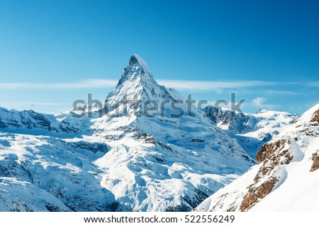 Scenic view on snowy Matterhorn peak in sunny day with blue sky and some clouds in background, Switzerland.