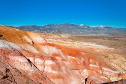 Scenic view over colorful red stone formations (eroded landform) of the mountains in Kyzyl-Chin valley aka Mars. Altai autumn landscape, Russia