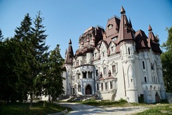 Scenic view over whimsical castle with red roof, surrounded by green trees. Beautiful historical landscape. Summer getaway vacation. Architectural sightseeing tour