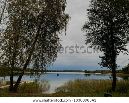 Photo of  Scenic view to lake with fishermen fishing in a boat in the background. Fishing season. Asveja lake, Lithuania
