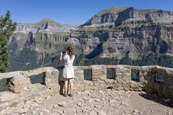 Scenic viewpoint over Ordesa Valley with turist girl on it. Ordesa y Monte Perdido National Park. Huesca, Aragon, Spain.