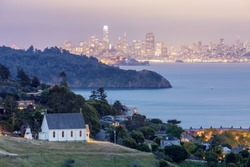 Scenic views of Old St Hillary's Church, Angle Island, Alcatraz Prison, San Francisco Bay and San Francisco Skyline at dusk. Shot from Tiburon, Marin County, California, USA.