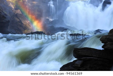 Scenic waterfall with rainbow in background.