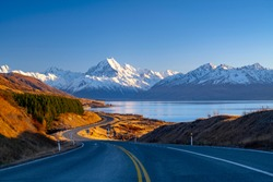 Scenic winding road along Lake Pukaki to Mount Cook National Park, South Island, New Zealand during cold and windy winter morning. One of the most beautiful viewing point of Aoraki Mount Cook.