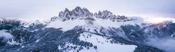 Scenic winter mountain landscape in Alps with aerial panoramic view of Geisler Peaks from Adolf Munkel trail in Zanser Alm, South Tyrol Dolomites with beautiful snow covered forest hills and summits