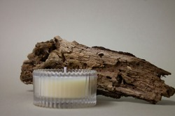 Scented candle made of soy, paraffin or wax in glass on a beige background and old tree bark. The concept of coziness, warmth and relaxation. Spa candle.