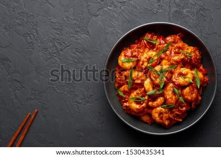 Schezwan Prawns in black bowl at dark slate background. Schezwan Prawns is indo-chinese cuisine curry dish with prawns or shrimps roasted in Schezwan Sauce.