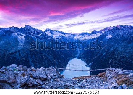 Schlegeis Basin is in province Tyrol in Austria, that surrounded by high mountain nature park Zillertal Alps. There is a suspension bridge at 2,388 meters asl. where tourists sit and view the basin. #1227575353
