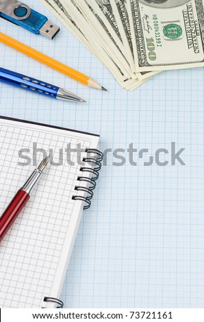 school accessories, dollars and checked notebook on graph grid paper
