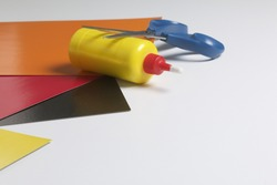 School accessories for creativity. Color paper, glue and scissors for applique. On a white background.