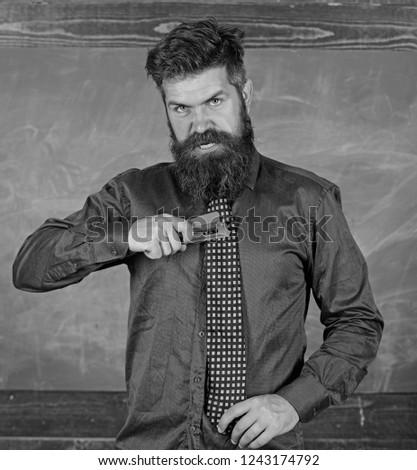 School accident prevention. School stationery. Man scruffy use stapler dangerous way. Hipster teacher formal wear necktie holds stapler. Teacher bearded man with pink stapler chalkboard background.