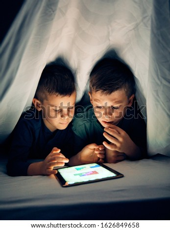 School age brothers having fun with a tablet together hiding under sheet at home Stock photo ©