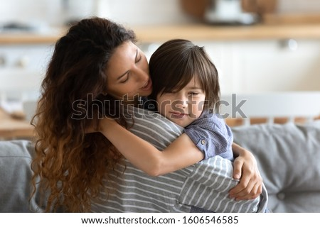 School age frustrated son receives psychological support from loving caring young mother, mom embracing little kid boy express care and love soothing him, motherhood, protection, sharing pain concept