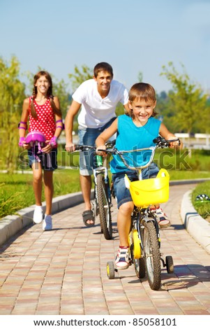 School aged boy and his father cycling, cheerful girl running behind
