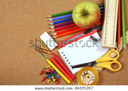 School and office supplies on cork board background
