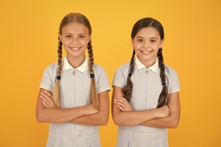 school authority. happy girls with pigtails. happy childhood. brunette and blond hair. best friends. vintage style. small confident girls in retro uniform. old school fashion. back to school.