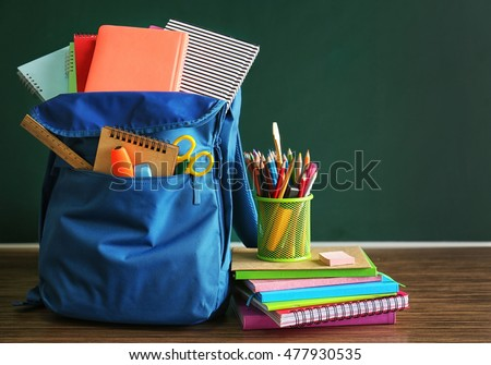 School backpack with accessories on chalkboard background Foto stock ©