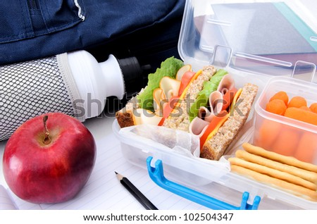 School bag, healthy lunch box and apple with books and pencil