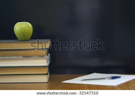 School books with apple on desk.