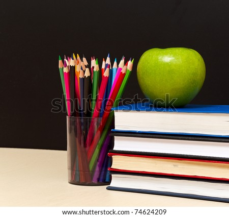School books with apple on desk, on black school board background