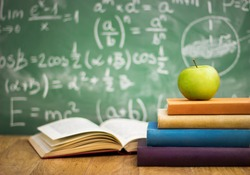 School books with apple on desk over green  school board background