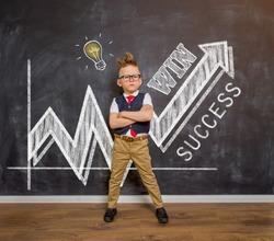 School boy against blackboard ready to win. Home education