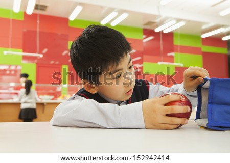School boy checking lunch bag in school cafeteria