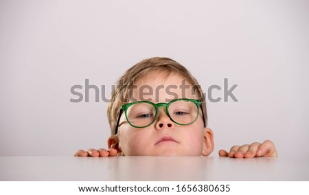 School boy in green eyeglasses. Funny child hiding behind the table Stock photo ©