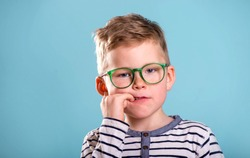 School boy nervously biting nails. Bulling and childhood psychology concept, Child boy in uniform, glasses and backpack isolated on blue. Kid portrait with finger in mouth