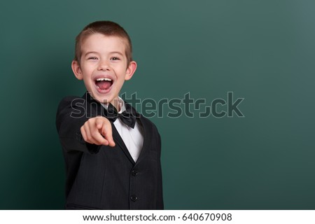 school boy point the finger near blank chalkboard background, dressed in classic black suit, group pupil, education concept #640670908