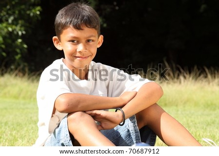 School boy sitting in the park on sunny day