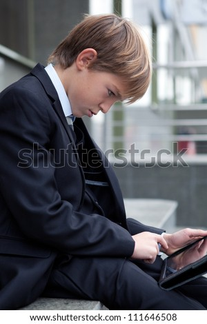 School boy with electronic tablet sitting,outdoor