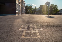School building and schoolyard in the evening. Hopscotch game on asphalt at the school yard playground.