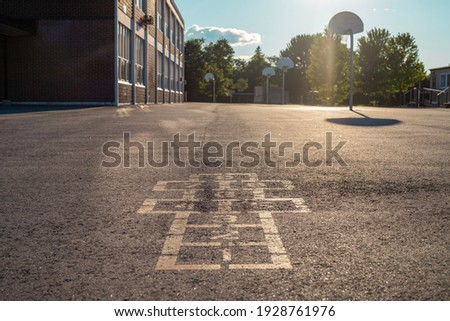 School building and schoolyard in the evening. Hopscotch game on asphalt at the school yard playground. Photo stock ©