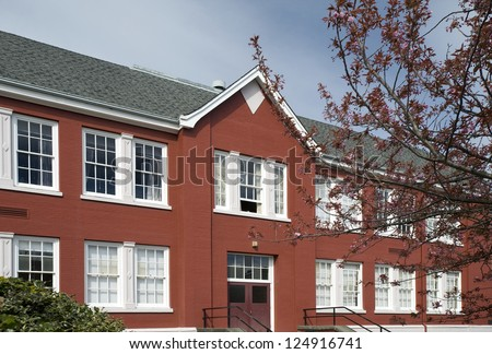 School building - Historic red brick school with tree in the blossom