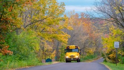 School bus driving along suburban street in fall; colorful trees in background; Missouri, Midwest