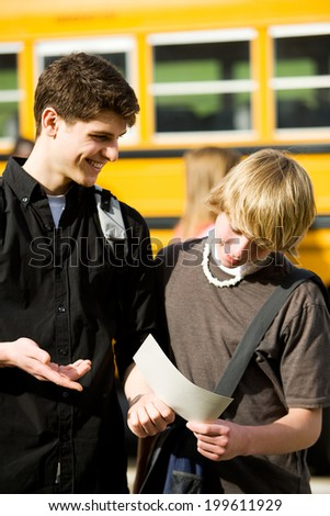 School Bus: Male Student Shows Friend Report Card
